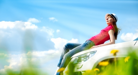 Beautiful young woman resting at bonnet of her car at flower field with blue cloudy sky in background photo