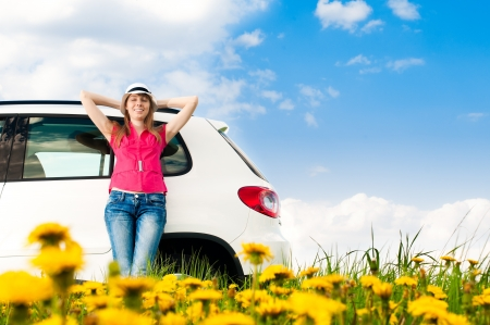 Beautiful young woman resting at side of her car at flower field with blue cloudy sky in background photo