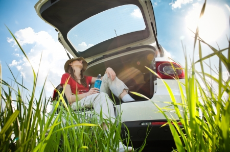 Beautiful young woman resting in boot of her car at  field with blue cloudy sky and sun in background photo