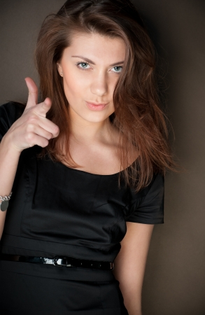 portrait of beautiful and sexy young woman in black dress with dark hair. Looking into the camera, pointing at you with her hand, dark brown background. photo