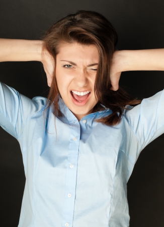 Beautiful young woman in blue shirt with dark hair screaming. Hands at her ears, mouth wide open, looking into the camera, dark background. photo