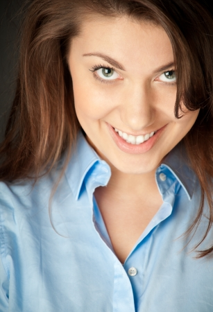 close up portrait of beautiful and sexy young woman in blue shirt. Smiling and looking into the camera, dark background. photo