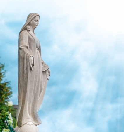 maria: Beautiful stone statue of woman. Blue cloudy sky in background. Sun with sun rays. Stock Photo