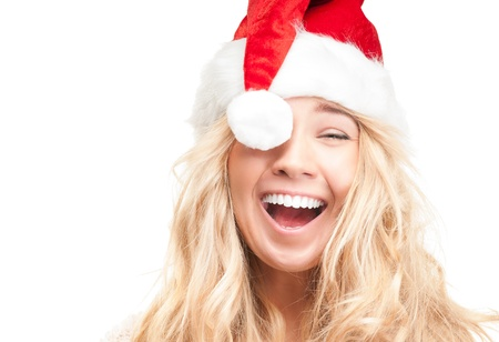 Portrait of joyful pretty woman in red santa claus hat laughing isolated on white background.  Stock Photo