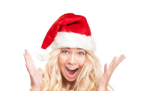 Portrait of shocked pretty young woman with open mouth in red santa claus hat on white background.  Stock Photo
