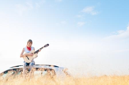年轻微笑的女孩坐她的有吉他的汽车在有麦田的手上在前景