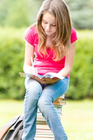 beautiful and happy young student girl sitting on pile of books, holding exercise book in her hands Stock Photo - 14858686