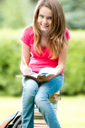 beautiful and happy young student girl sitting on pile of books, holding exercise book in her hands Stock Photo - 15183854