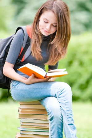 beautiful and happy young student girl sitting on pile of books, holding book in her hands and reading. Stock Photo - 14858981