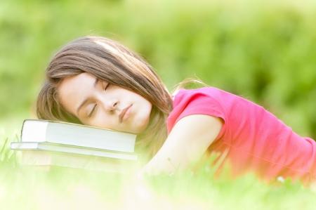 agotado: chica joven estudiante hermoso y cansado tirado en la hierba verde, pila de libros bajo su cabeza, con los ojos cerrados. Verano o primavera parque verde en el fondo