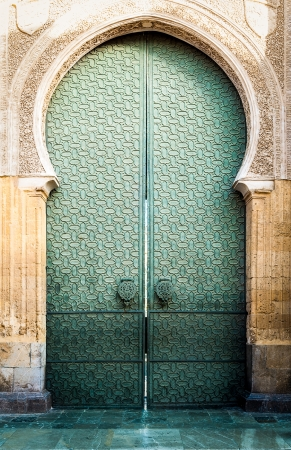 Famous landmark in Spain. Beautiful cathedral Mezquita of Cordoba, Andalucia. Green door with arch in old arabic style. Traditional spanish architecture. Religious and tourist place in Europe. Stock Photo