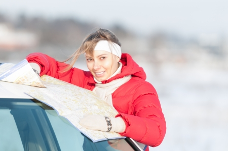 Beautiful girl standing near car with map. Brightwinter day, snow in background. Woman looking into camera and smiling,wearing red jacket. Active outdoor and travel on car in winter. Stock Photo - 15045444