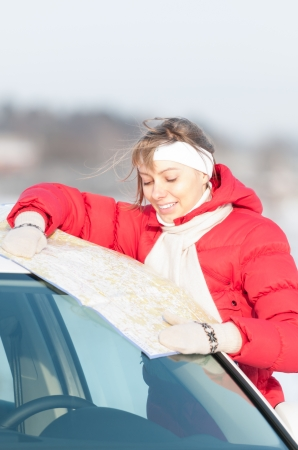 Beautiful girl standing near car with map. Bright