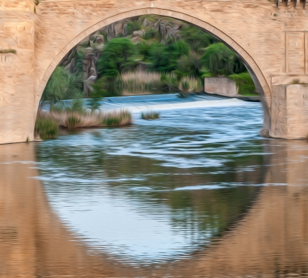 stone bridge: Famous bridge in Toledo, Spain. Arch and reflection in water form big circle. River running fast. Beautiful nature with green trees in background. Popular place for tourism in Europe.