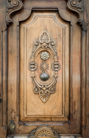 Part of door adorned by vintage ornate patterns  Front view of wooden door fragment with stylish symmetrical carvings on it  Entry is decorated with flowers, leaves, curls and circles made of wood  photo