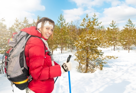 Beautiful girl in red jacket standing with backpack and ski poles. Happy smiling woman enjoys bright winter day. Blue sky with clouds, snow and forest in background. Active sport and outdoor activity. Stock Photo - 15045451
