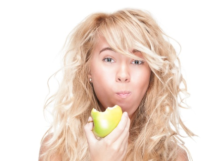 chewing: Beautiful woman chewing green apple. Young girl holding fresh fruit. Model isolated on white background. Motivation for diet and healthy lifestyle. Positive person with happy facial expression. Stock Photo