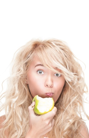 Beautiful woman chewing green apple. Young girl holding fresh fruit. Model isolated on white background. Motivation for diet and healthy lifestyle. Positive person with happy facial expression. 版權商用圖片