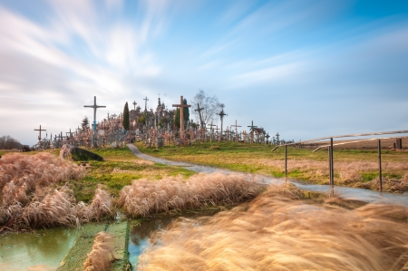 Famous hill of crosses near Siauliai, Lithuania, Europe. Yellow grass in foreground and blue cloudy sky in background.