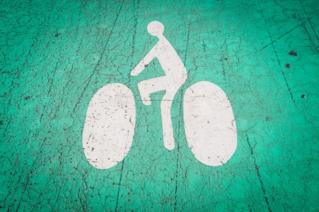 Icon of the bicycle with the cyclist on it on the ground. White symbol, green background. Nice, France, Europe. photo