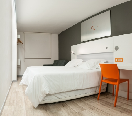 Beautiful stylish inter in modern style. Elegant design of furniture. Clean empty hotel room with double bed. Contrast of pastel colors and bright details. Night with closed window and light on. Stock Photo - 15086772