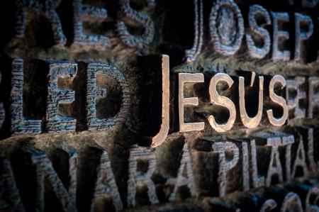 letras de oro: Texto escrito con letras de oro. El nombre de Jesús se destaca entre otros nombres de santos. Hermosa y antigua pared de la iglesia en colores oscuros. Lugar sagrado y religioso. Destino famoso para los turistas. Foto de archivo