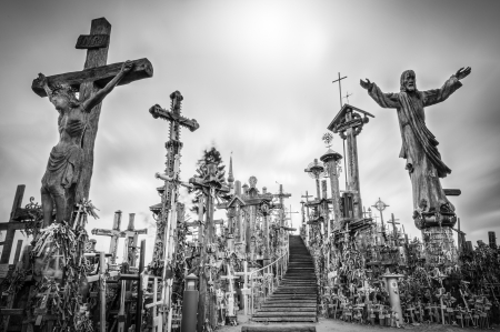 Hill of crosses in Siauliai, the city of Lithuania. Old stairway goes to gray sky. Stairs lead to the top of hill. Crosses and statues of saints near. Sun shines weakly, so place looks mysterious. photo