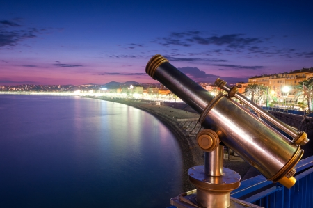 Sunset view of the coast line with beaches of Nice city. Tourist telescope in foreground and blue evening sky and the sea in background. Nice, France, Europe.
