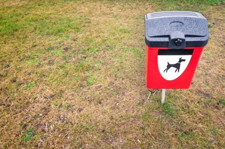 public waste: Plastic garbage bin for pets dung with black and white dog symbol on it. Bright red box for animals waste on green grass lawn in park area. Public responsibility for clean environment.