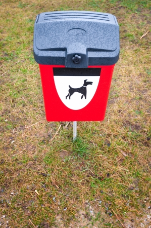 Plastic garbage bin for pets dung with black and white dog symbol on it. Bright red box for animals waste on green grass lawn in park area. Public responsibility for clean environment. photo