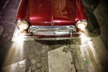 shiny car: Kleine auto in retro stijl met voorbumper. Rode vintage vervoer. Fel licht van twee werkdagen ronde koplampen verlichten de weg. Reflectie van huis op glanzende auto motorkap. Lange rit 's nachts.