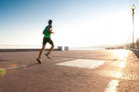 hombre deportista: Hombre que se ejecuta en el paseo mar�timo en la playa. El desenfoque de movimiento en el corredor, un mont�n de espacio de la copia (Niza, Francia, Europa).