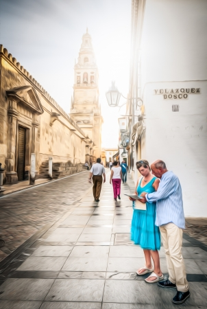 Couple standing on street of Cordoba in Spain. Famous architecture of buildings. Wall with door and beautiful tower. Bright sunny day and people walking on road. Popular place for tourists. photo