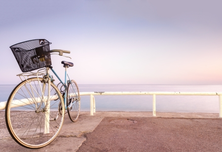 seasides: Old and vintage bicycle at the railing near the sea. Blue sea and sunset sky in background. A lot of copy space. Nice, France, Europe.