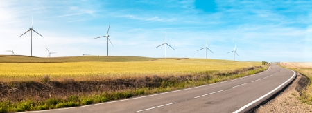 Wind turbine on green and yellow field. Empty road in foreground, blue