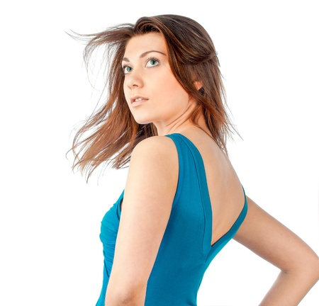 Beautiful and sexy young woman in blue dress with dark hair flying. Looking away from the camera, isolated on white background. photo