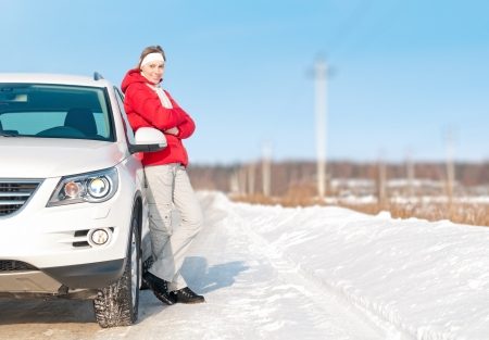 winter day: Young girl in red jacket standing near big white car and smiling. Happy road trip with beautiful woman. Active outdoor and winter travel by car. Bright day with clear sky and snow around. Stock Photo