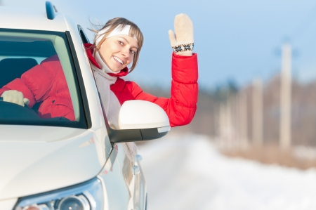 Young woman drives white car. Blonde attractive girl in red jacket. Positive and happy person. Active tourist on winter vacation. Cold and sunny winter day. Healthy outdoor leisure in north region.