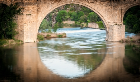 bridge over water: Famous bridge in Toledo, Spain  Arch and reflection in water form big circle  River running fast  Beautiful nature with green trees in background  Popular place for tourism in Europe  Stock Photo