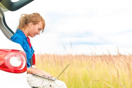 Young happy girl sitting and working on computer  Beautiful woman near car in meadow holding laptop  Person working outdoor  Tail light of car in foreground and field with sky in background Stock Photo - 16249817