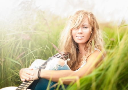 sexy guitar: Pretty girl with guitar sitting on ground  Beautiful woman with blonde hair holding musical instrument and smiling  Green grass as background  Sunny summer day  Outdoor activity for young people
