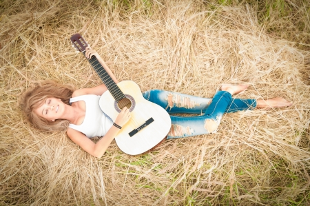 dream land: Beautiful woman dreaming with closed eyes  Pretty girl lying in meadow with guitar  Person holding musical instrument  Happy smiling girl with carefree lifestyle  Outdoor activity for young people  Stock Photo