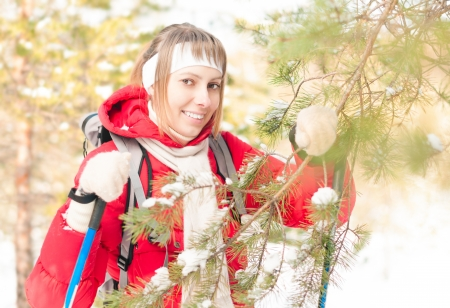 Beautiful girl in red jacket standing with backpack and ski poles  Happy smiling woman enjoys bright winter day  Winter snowy forest in background  Active sport and outdoor activity Stock Photo - 16249858