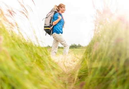 Happy smiling woman walking in field  Green grass in foreground and clear sky in background  Girl in sport clothes hiking with backpack  Blonde crossing meadow  Outdoor activity and active lifestyle  Stock Photo - 16249806