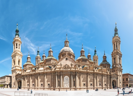 pano: Basilica of Our Lady of Pillar with blue sky as background  Famous church with beautiful ornate architecture  Old majestic building with two high towers  Popular tourist place in Spain, Europe  Pano