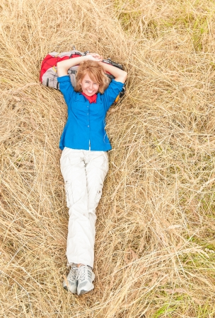 Young girl lying on grass in field  Beautiful woman in sport clothes resting with backpack under head  Happy smiling person relaxing in meadow  Outdoor activity and active people  Stock Photo - 16249855