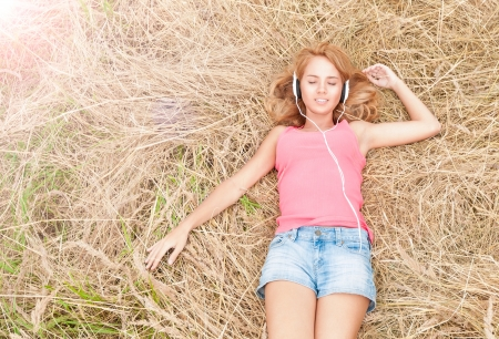 listen music: Beautiful girl relaxing in headphones outdoors  Pretty smiling woman with closed eyes listening to music lying on hay in field  Harmony of human and nature  Countryside