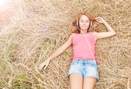 Belle fille de détente en plein air dans le casque Jolie femme souriante, les yeux fermés écoutant de la musique couché sur le foin dans Harmony domaine de la Campagne de l'homme et de la nature Banque d'images
