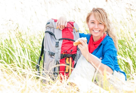Young pretty woman tourist with backpack having lunch in wheat field background  Happy and smiling girl on halt  Tourism travelling and hiking outdoors in summer  Healthy lifestyle  photo