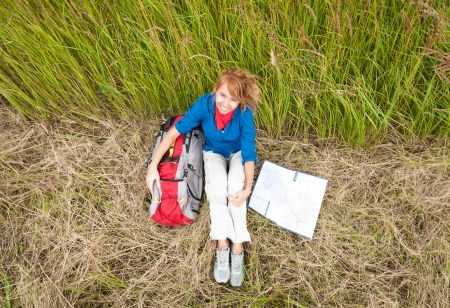 Young pretty female tourist with backpack and map having stop in field  Happy and smiling girl on halt sitting on dry grass  Tourism travelling and hiking outdoors in summer Healthy lifestyle  photo